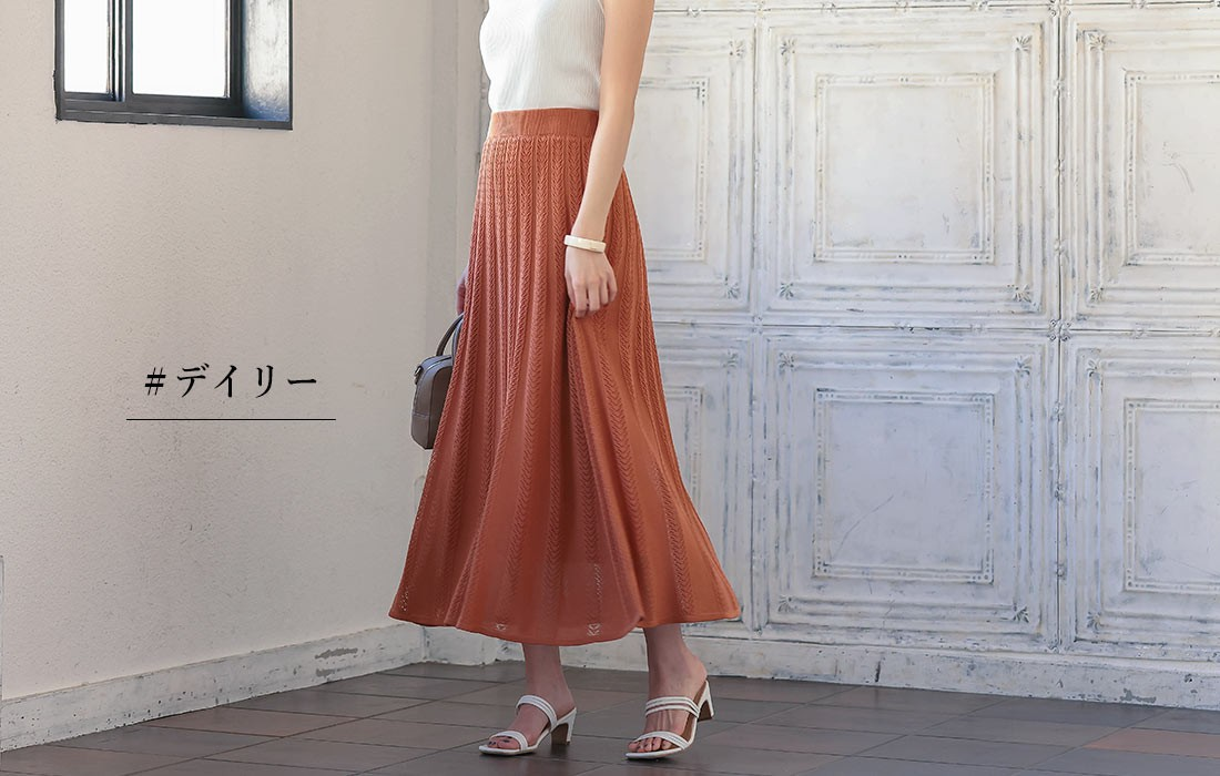 レンガ色のロングスカートを履いた女性